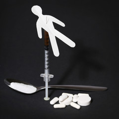 Drug Addiction Concept. Paper man with syringe and pills