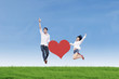 Couple jumping with heart card
