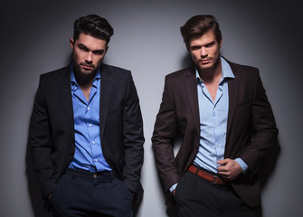 serious male models posing against gray wall