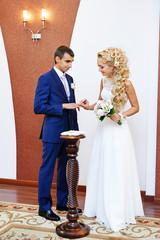 Happy bride wears wedding ring her groom