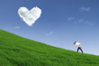 Guy giving piggyback ride on hill under heart cloud