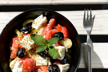 Mediterranean salad with feta cheese in black bowl