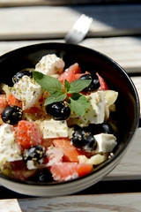Mixed vegetables salad with cheese in black bowl
