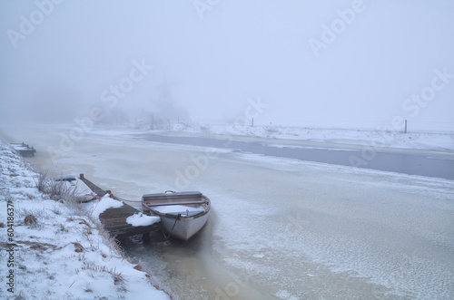 boat on frozen river in foggy winter day