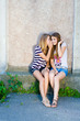 Two happy beautiful teenage girls sharing secret on summer day
