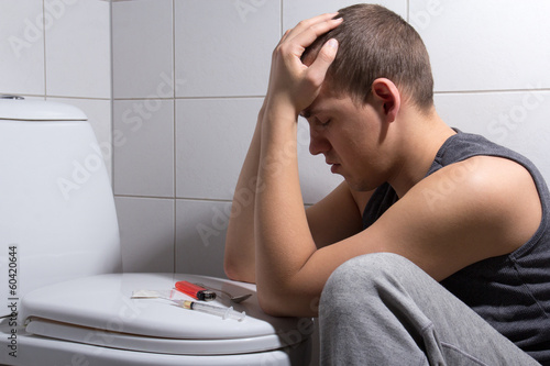 depressed man with heroin addiction sitting in wc room