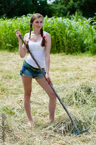 Beautiful young woman working with rake on dry hay on summer day