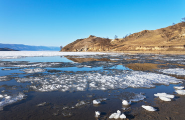 Sunny day at Baikal Lake. Spring floating of ice