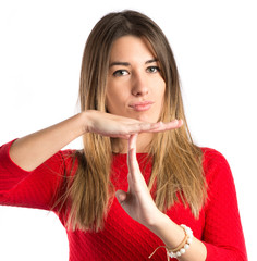 Young girl making time out gesture over white background