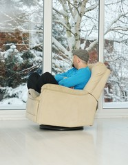 Young man relaxing on a white sofa at home by winter snow time
