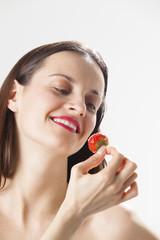 Junge Frau mit einer Erdbeere