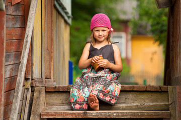 Beautiful little five-year girl on the porch of a village house
