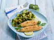 breaded fish with broccoli and olives, selective focus