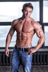 Muscular young sexy guy posing in jeans and naked torso