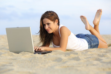Teenager girl browsing her laptop lying on the beach