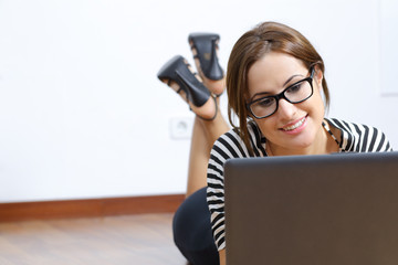Beautiful woman browsing a laptop lying on the floor