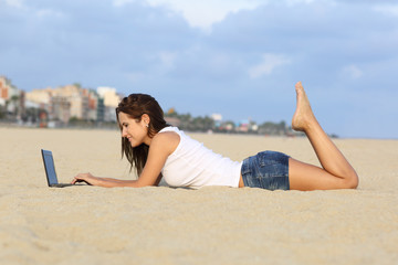 Teenager girl browsing her laptop lying on the sand of the beach