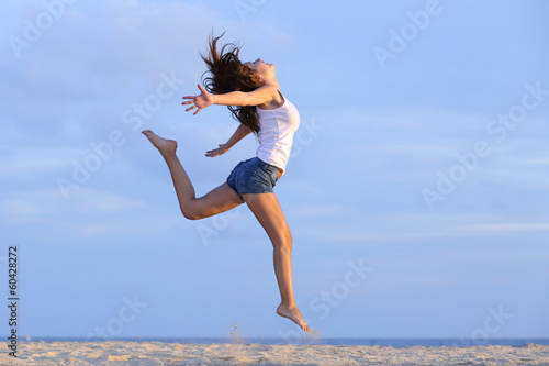 Woman jumping on the sand of the beach