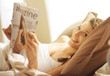 Woman relaxing in bed with magazine