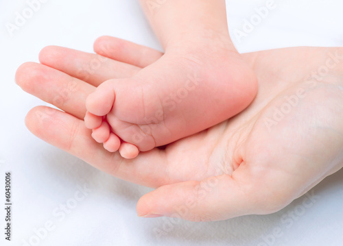 Baby Feet in Mother Hands. Newborn Baby and Mom