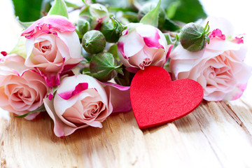 roses and heart are on a wood background