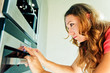 Beautiful woman moving the timer knob on the oven