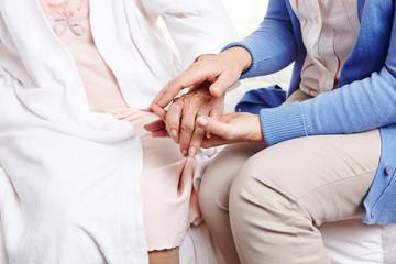 Frau hält Hand einer Seniorin