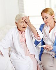 Frau misst Fieber bei Seniorin mit Grippe