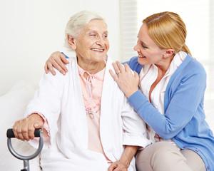 Lachende Seniorin schaut ihre Tochter an