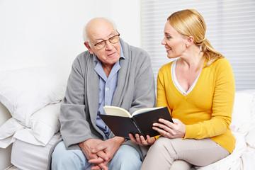 Frau liest altem Mann ein Buch vor