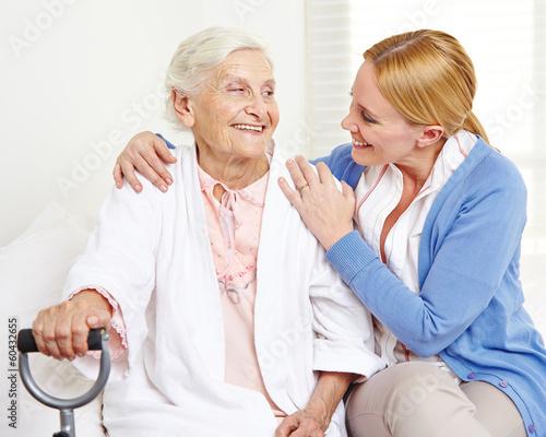 Leinwanddruck Bild Lachende Seniorin schaut ihre Tochter an