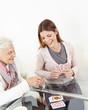 Leinwanddruck Bild Seniorin spielt mit Enkeltochter Karten
