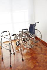 Leerer Rollstuhl und Gehhilfe im Pflegeheim