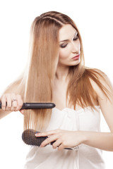 redheaded girl straightens the hair using a hair straightener