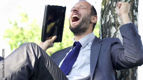 Joyful young businessman with tablet computer, slow motion shot