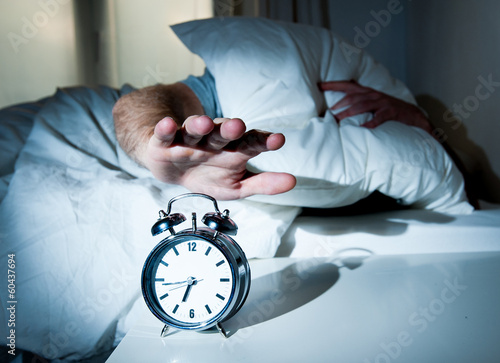 sleeping man disturbed by alarm clock early morning