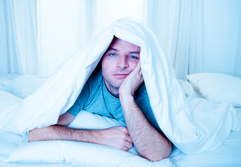man in bed with eyes opened suffering sleeping disorder