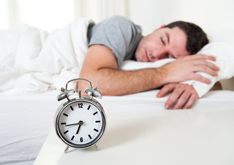 Young attractive man sleeping on bed