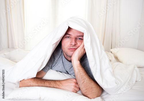 man in bed with eyes opened suffering insomnia