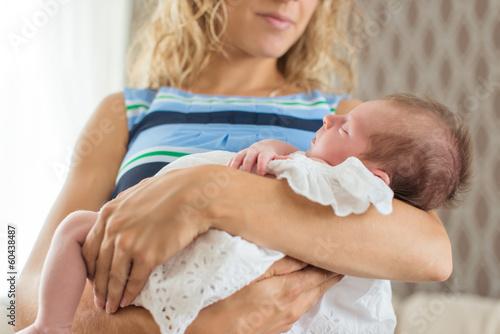 Newborn in a christening dress sleeping in her mother
