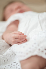 Defocused hand detail of a sleeping newborn baby girl
