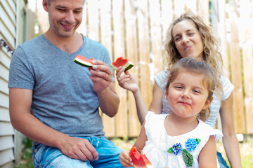 Parents and little girl having watermelon on a picnic