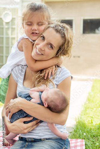 Mother and two daughters hugging outside