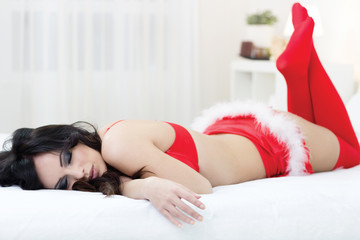 Young sexy santa lying on bed