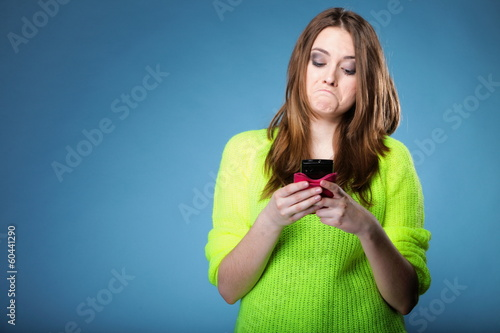 Funny girl with mobile phone reads message