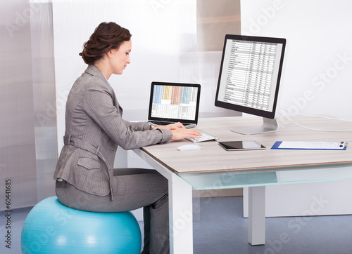 Woman Sitting On Pilates Ball Using Computer