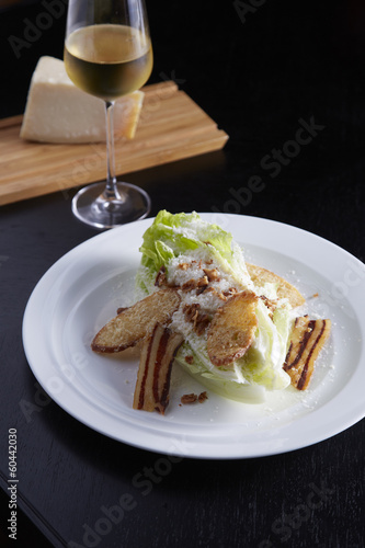 Caesar Salad on white plate with wine