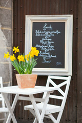 Table of a street cafe with yellow jonquils
