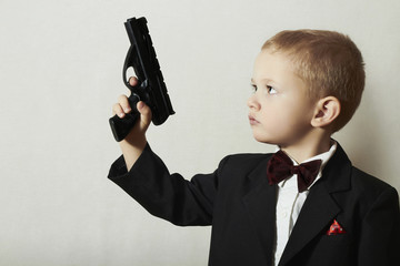 Fashionable Little Boy in Bow tie.Stylish Agent.Child with Gun.