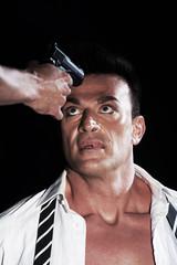 uomo con pistola alla fronte